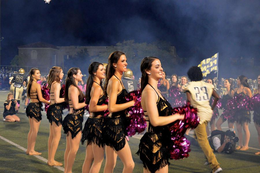 The Danceros cheer on the football team at the start of the game.