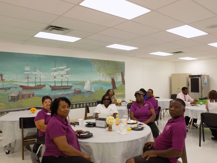 Bus drivers gather at a table in the cafeteria to partake in the appreciation breakfast.