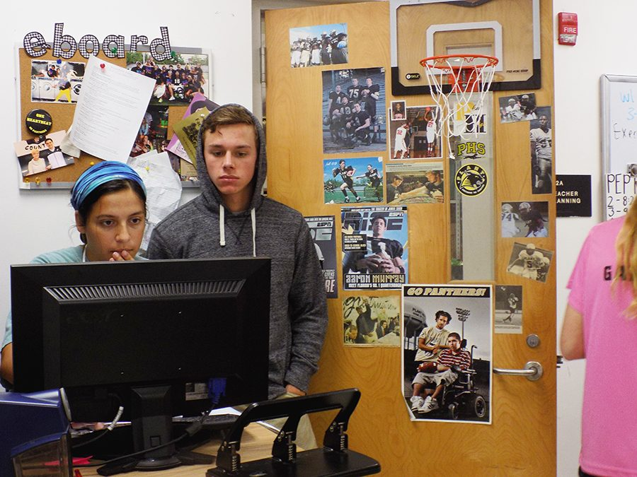 E-board members, Lena Diasti and Hunter Owens, junior and senior, search on the computer for Homecoming accommodations such as a DJ.
