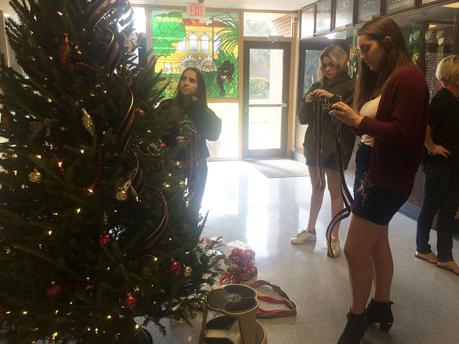 Decorating the Angel Tree, Alyssa Stern and Kinley Larson, seniors and Peyton Purdy, junior, help to advertise the charity drive.