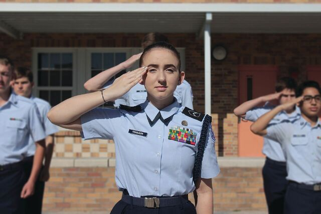 Senior Vanessa Freggusen stands in the gym courtyard while leading a flight in a thirty-step drill sequence.