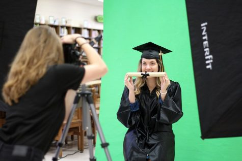 Posing for the camera, senior Emily Atkinson holds onto a prop for graduation portraits in the media center Friday Aug. 17.  The photo company will be on campus Sept. 11 and Sept. 28 to take pictures of the rest of the seniors.