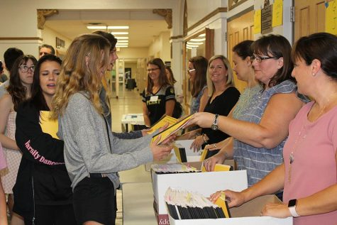 At senior night in the auditorium Aug. 23, a volunteer hands Elise Kern a packet. Enclosed in these packets were the contents of the meeting, such as which college reps were speaking and how to work on a resume.
