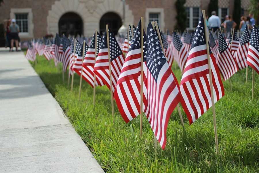 In preparation for Patriot Day, American flags are staked in the green space at the front of the school Sept. 10.  Students and faculty alike gathered after its installment to observe the display commemorating the anniversary of 9/11.