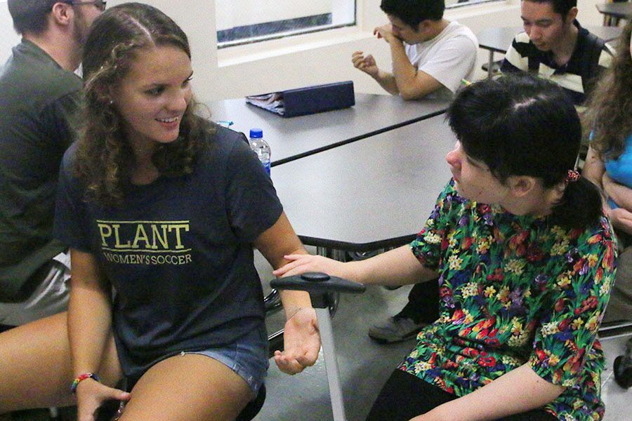Reaching out to sophomore Lauren Webster, freshman Chiara Melcher greets her during the Best Buddies club meeting Sept. 26 in the cafeteria. The club's matching party is Oct. 13 where everyone will be assigned a Buddy for the year.