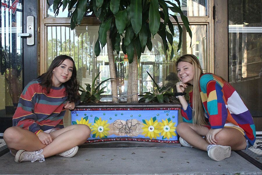 """Using acrylic paint, seniors Rebecca sierra and Amanda Phillips paint a transformation of hands going into flowers, the hands representing the planting of roots. They chose this design because of their interpretation of the theme """"plant a seed watch it grow."""""""