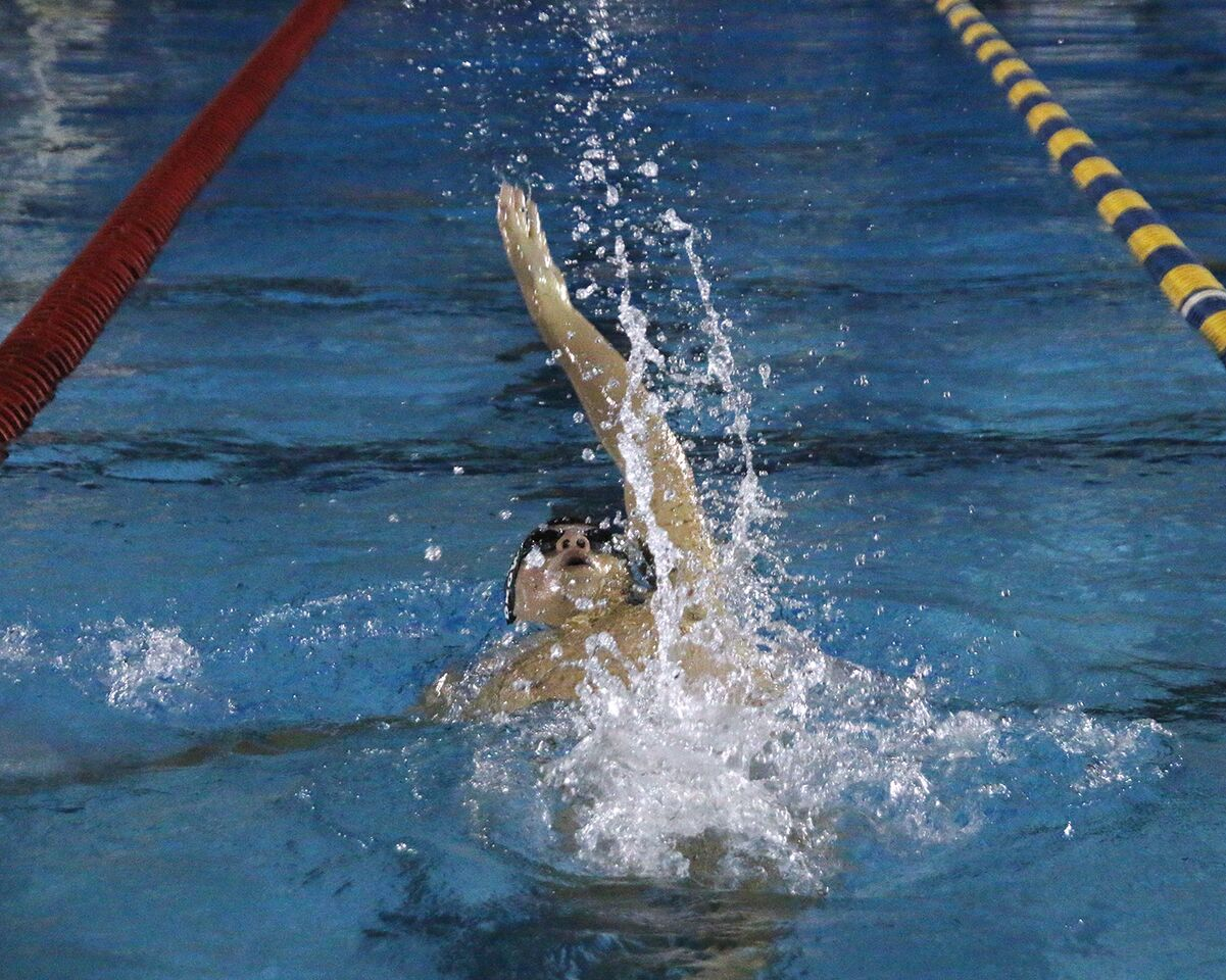 Swimming backstroke, junior Joel Brown swims the boys 200-yard medley relay at Bobby Hicks Pool Oct. 11. Brown placed second in his heat with his team against Wharton High School.