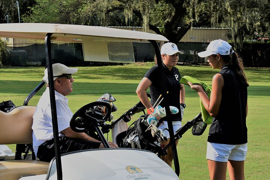 With the players in view, sophomores Annika Johnson and Leila Ossi discuss their game plan strategies Sept. 13. The girls golf team emerged victorious 127-150 at Temple Terrace Golf and Country Club and counted 6 holes due to the weather.