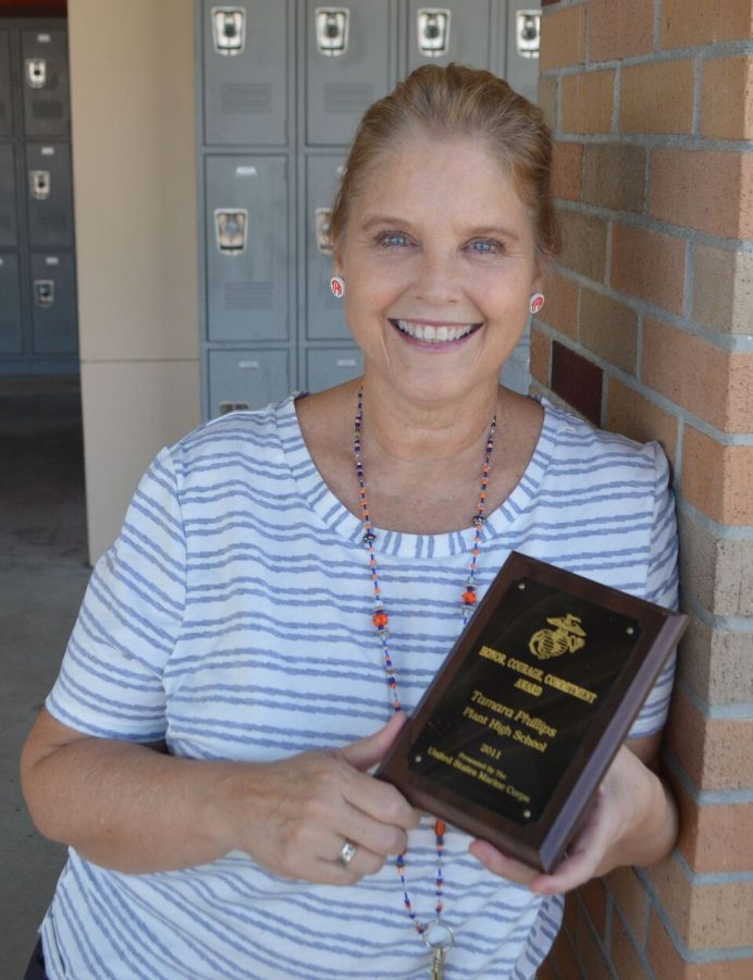 Rewarded by the United States Marine Corp, social studies teacher Tamara Phillips poses with her Honor, Courage, Commitment Award. Phillips received her award during a season football game in 2011, after having survived bone cancer that resulted in surgery and a permanent disability.