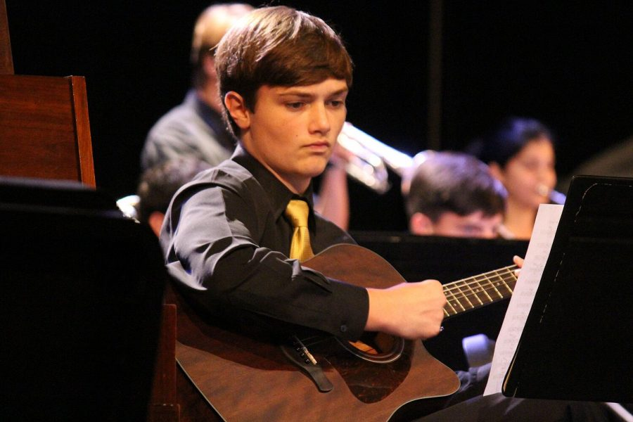 Along with the jazz band, sophomore Gabe Howard plays guitar during their show Thursday, Oct. 4 in the auditorium. The jazz band received a Mark of Excellence award, being one of the two groups nationally recognized.