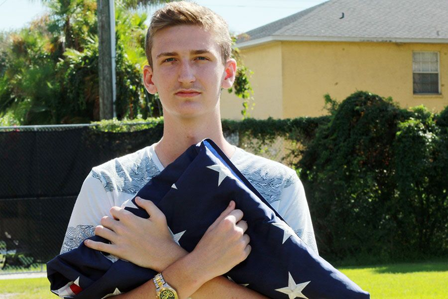Holding the flag, junior Joseph Cacciatore takes his position for ROTC. Joseph was appointed the color guard commander and said that the main goal of ROTC is to promote citizenship at the school.