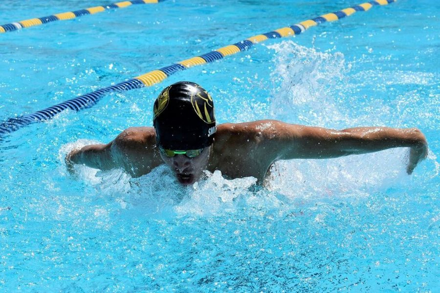 Halfway through the race, junior Jackson Smith is about to touch the side of the pool. Smith placed fourth in the Swimming County Championship for the men's 100-yard butterfly event Friday, Oct. 5.