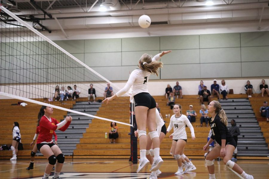 Approaching to hit the ball, freshman Lily Frierson spikes down, securing a point for the varsity team at Freedom High School Oct. 15.  The team won against Leto High School 3-0.