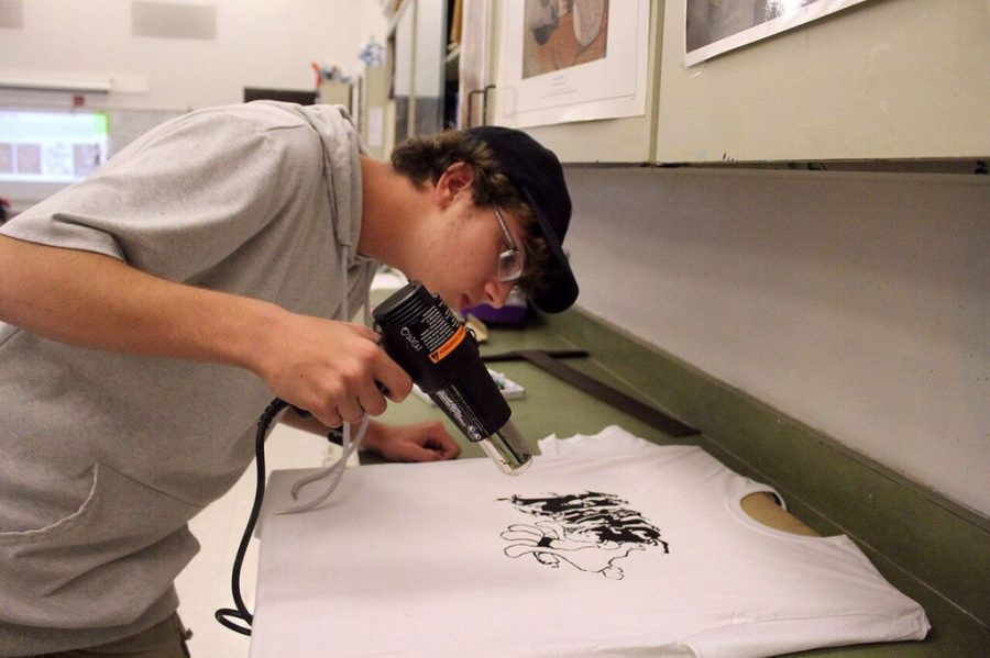 Drying his shirt, junior Cameron Harnett waits for the design to be dry before removing it from the table. The National Art Honors Society met in the art room Tuesday, Oct. 16 to make club shirts.