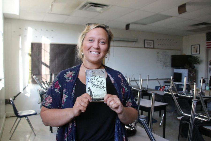 """Holding a copy of 'To Kill a Mockingbird,' English teacher Cristalyn Stokes shares her passion for mixing her profession with theater. """"I think that everyone should have some sort of exposure to anything musically related,"""" Stokes said."""