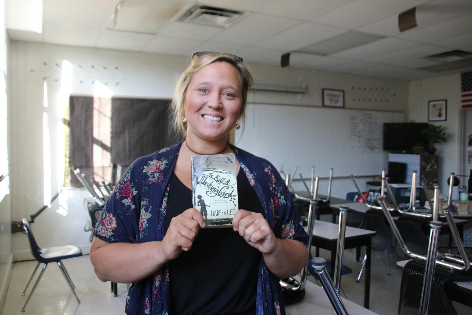 "Holding a copy of 'To Kill a Mockingbird,' English teacher Cristalyn Stokes shares her passion for mixing her profession with theater. ""I think that everyone should have some sort of exposure to anything musically related,"" Stokes said."