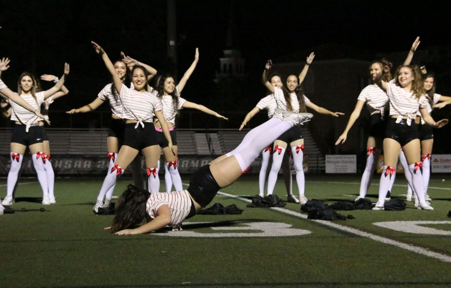 While senior Katy Kasper does the worm across the field, the Zeta girls throw up their hands during Panther Prowl at Dad's Stadium Oct. 24.  Kasper has been a member of Zeta for two years.