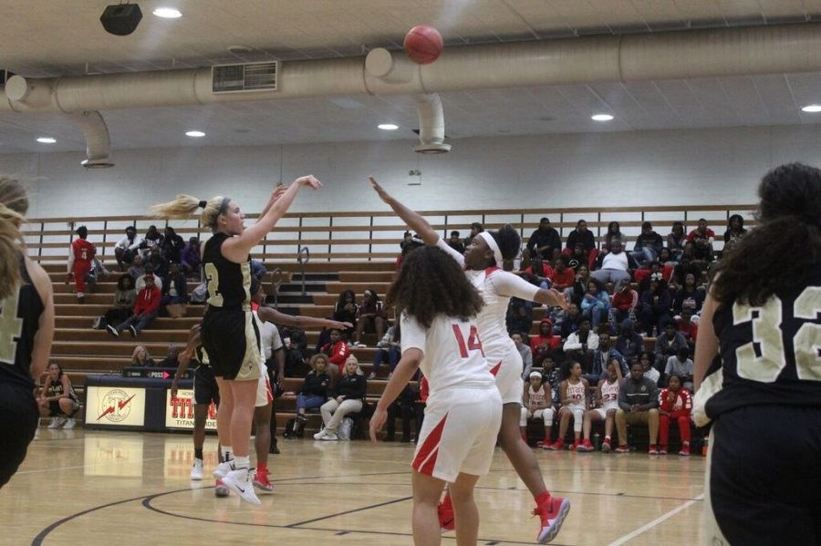 As her opponent attempts to block the ball, junior Honor Culpepper takes a jump shot Tuesday, Nov. 27 at Tampa Bay Tech. The girls varsity basketball team won the game 45-40.
