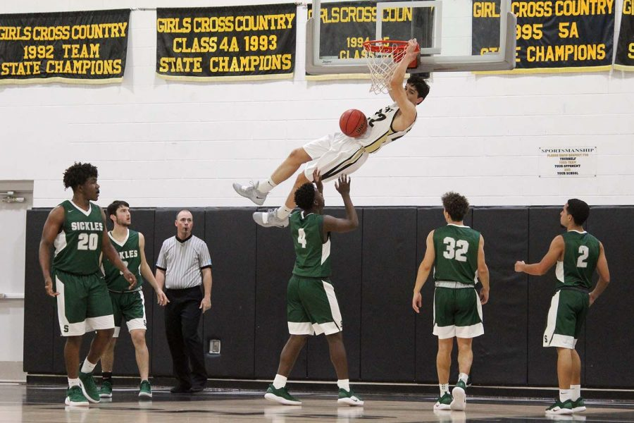 Swinging from the hoop, senior Logan Morrissey dunks the ball in the gymnasium Jan. 22. The boys basketball team beat Sickles High School 64-51.