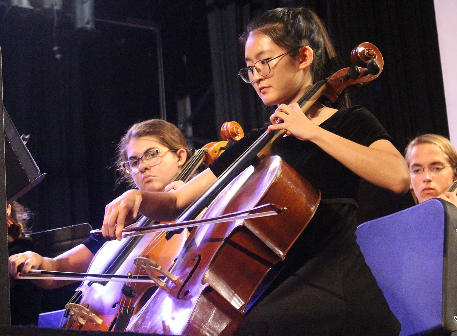 Bowing a section of American Salute composed by Morton Gould, sophomore Morgan Austrich and senior Ashley Cha sit first and second chair Monday, Feb. 11 in the auditorium. Both players have been in Philharmonic since their freshman years.