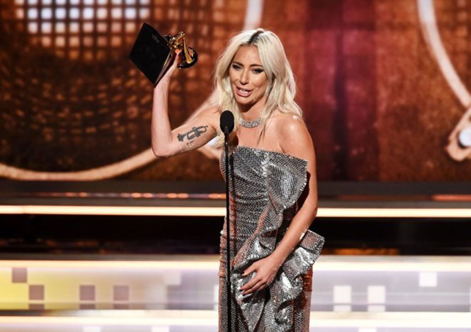 "Winning two Grammy awards, Lady Gaga wears a stylish silver sequined dress from Celine by Heidi Silmane Jan. 10. She won best song for the song ""Shallows"" in a"