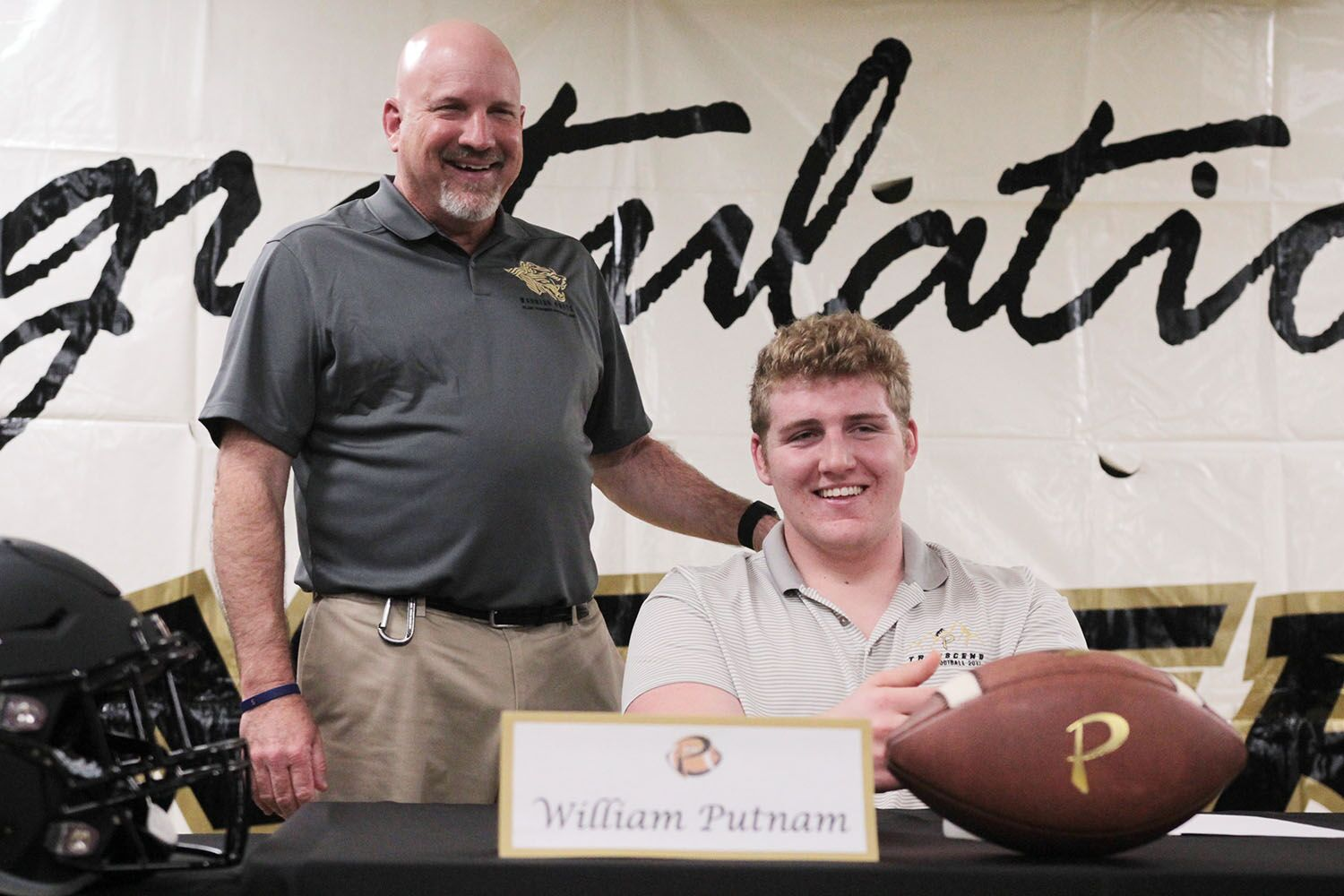 """Calling him a """"once in a lifetime player,"""" head coach Robert Weiner introduces senior offensive lineman William Putnam Dec. 20 in the field house. Putnam announced he had signed with Clemson University by pulling out a Clemson hat and placing it on his head."""