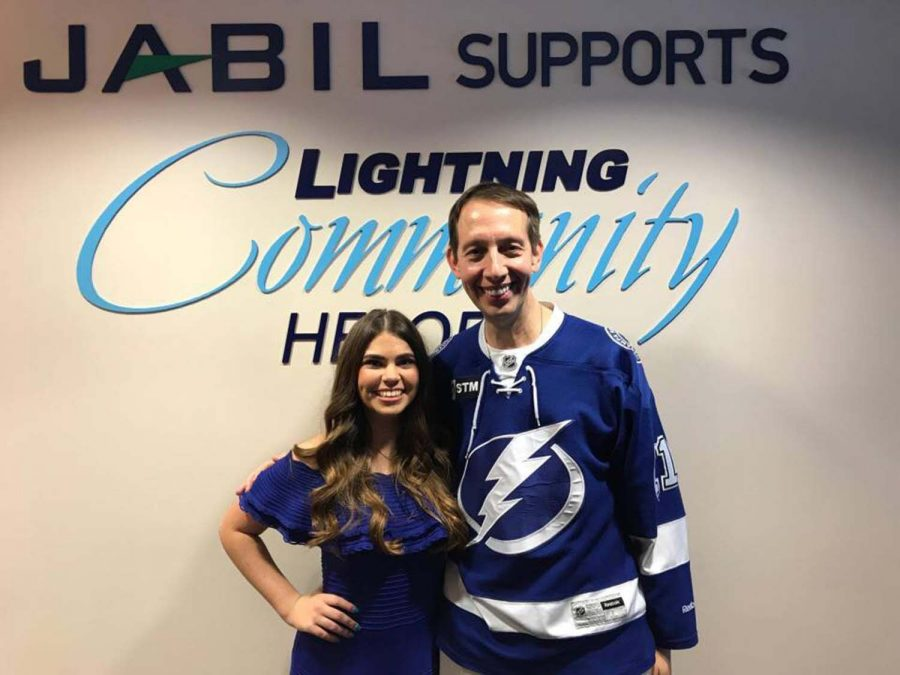 Standing with her pastor, senior Emily Surak receives the Lightning Community Hero award Dec. 8th. Her work with the Crisis Center of Tampa Bay was recognized at the event.