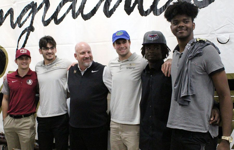 Following+the+signing+of+their+letters+of+intent%2C+seniors+Caleb+Faris%2C+Enrique+Jerico+DeJesus%2C+Jude+May%2C+Romain+%22Smoke%22+Mungin+and+Cameron+Shaw+stand+alongside+head+coach+Robert+Weiner+in+the+media+center+Wednesday%2C+Feb.+6.+They+all+announced+their+decisions+to+play+Division+I+football+on+National+Signing+Day.+