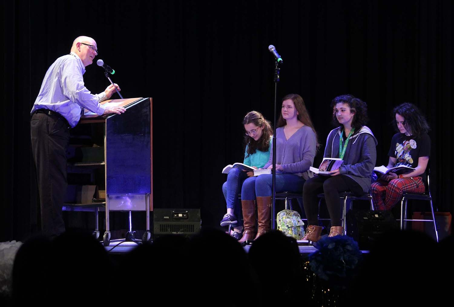 Reading out to the crowd, Matthew Penn along with a small group of students perform a skit at Faculty Idol Jan. 31 in the auditorium. The act was a poem which spoke about typical situations in a classroom.