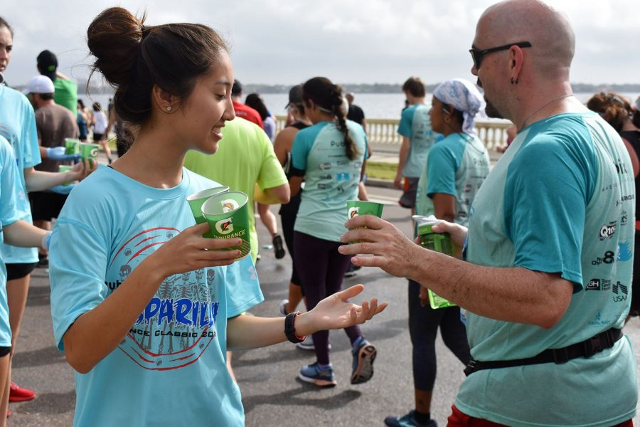 Smiling, sophomore Hannah Cohen distributes Gatorade Feb. 24. Various teams worked for hours in the morning for the Gasparilla Distance Classic.