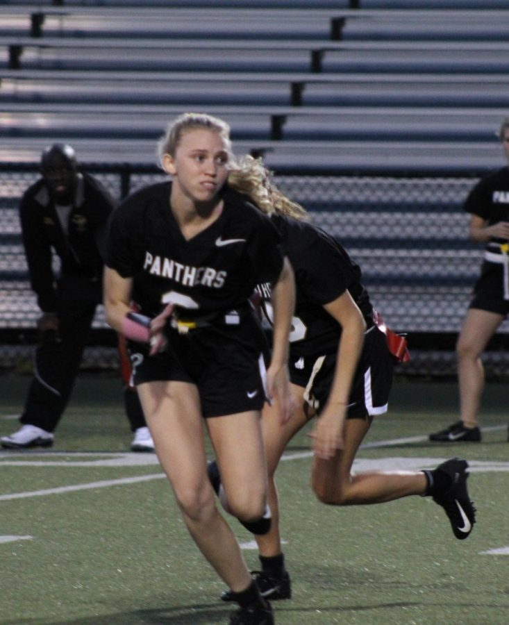 Running towards offense, junior Birdie Frierson attempts to pull a flag March 28 at Dad's Stadium. Frierson has been in the flag football program since her freshman year.