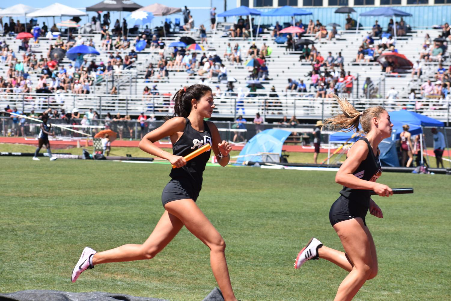 Grasping+the+baton%2C+freshman+Arlie+Rubin+catches+up+to+a+runner+April+27+at+George+Jenkins+High+School.+Rubin+raced+the+third+leg+of+the+4x800+and+qualified+for+states+in+the+1600-meter+later+in+the+day.+