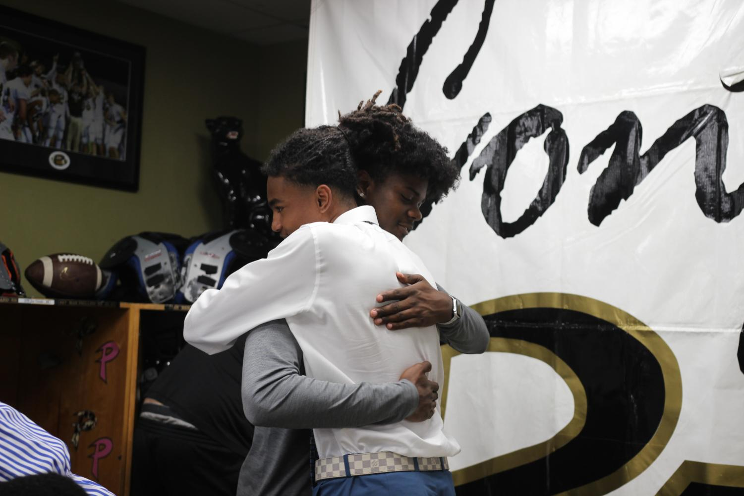 Following+the+ceremony+senior+Julien+Kee+embraces+teammate+Cameron+Shaw+before+they+pose+for+a+picture+April+17+in+the+field+house.+Shaw+signed+on+National+Signing+Day+and+will+be+attending+University+of+Central+Florida.++