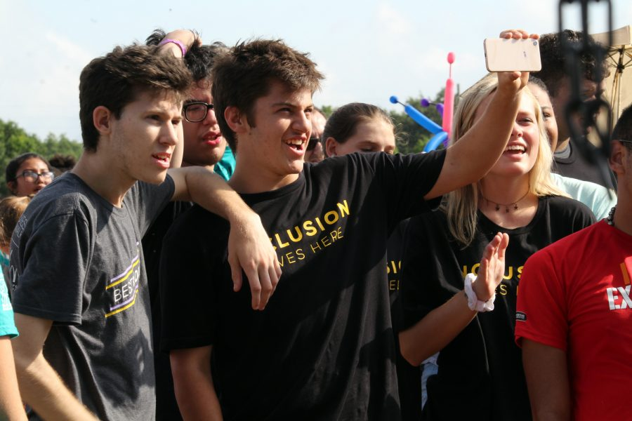 Taking a picture, Best Buddies members pose in front of a painted bus Sunday, May 5 at the Raymond James Stadium. The bus was set up for participants of the event to finger paint on it.