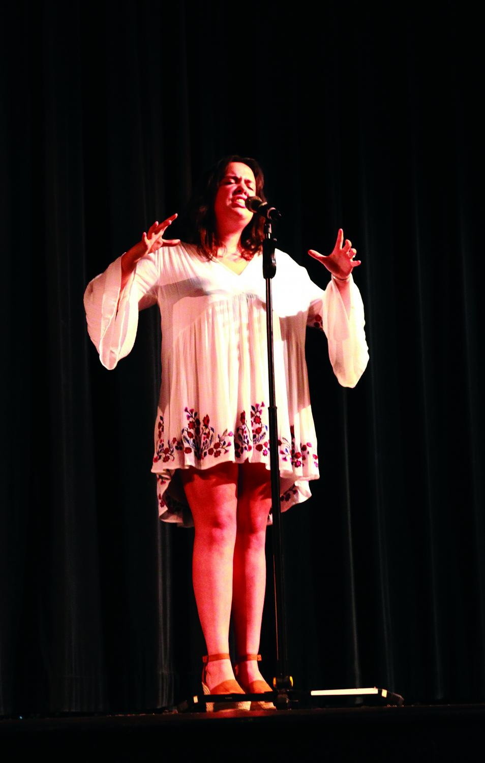 Arms+in+the+air%2C+junior+Megan+Martinez+sings+at+Be+the+Voice+in+the+auditorium+April+23.+Martinez+won+first+place+in+the+competition.+