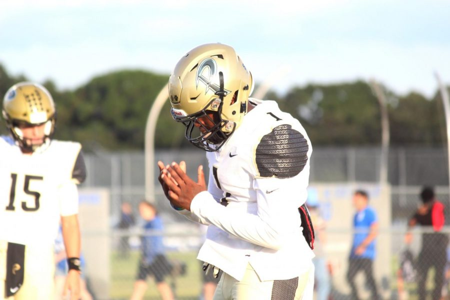 Clapping his hands, senior wide receiver Frank Murphy leads pregame warm ups. The varsity football team fell to Armwood 38-3.