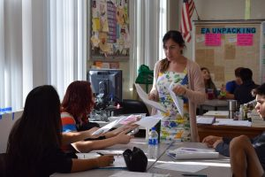 English teacher Stacey Malin collects work from her students Tuesday, Aug. 27. Malin began her teaching career in New York, working at an international school teaching students English.