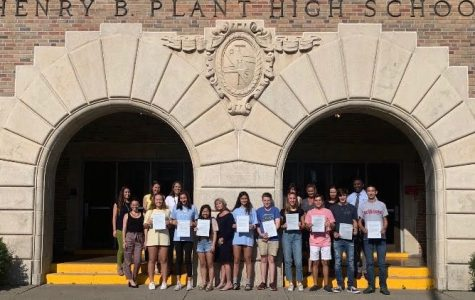 Facing forward, the semifinalists posed for a picture in front of Plant High School. They are 9 out of the 16,000 semifinalists selected from an initial entrant pool of 1.6 million.