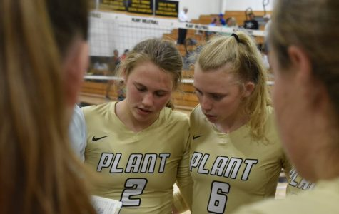 Huddled with the volleyball team, sophomore Lily Frierson and senior Birdie Frierson listen to their coach at a time-out at the Alonso game Sept. 12 in the gym. The sisters began playing volleyball after watching their two older sisters enjoy the sport, too.