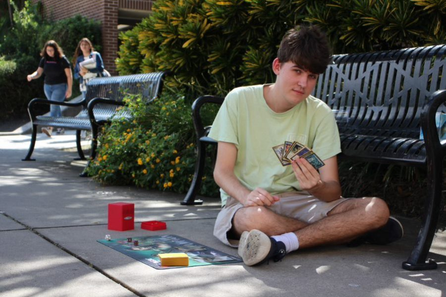 Wielding spell-powered cards, senior Riley Shofner prepares his move for board game, Magic: the Gathering. Riley began playing and competing in Magic: the Gathering in middle school.