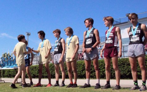 Shaking his teammate's hand, senior Lee Gibson accepts his second place ribbon at the North Port Invitational Sept. 21. The team placed first at this meet with a team average time of 16:17.