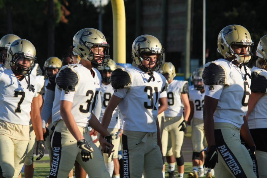 Holding hands as they walk onto the field, junior defensive backs Christian Maxie and Matthew Rogero get ready for the game. The varsity football team fell 38-3 versus Armwood High School in the second game Friday, August 23.