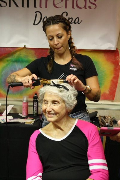 Smiling while getting her hair curled, an attendee of the pamper party gets her hair styled by another sponsor of the event. The women who attended received free products as well as their makeovers.