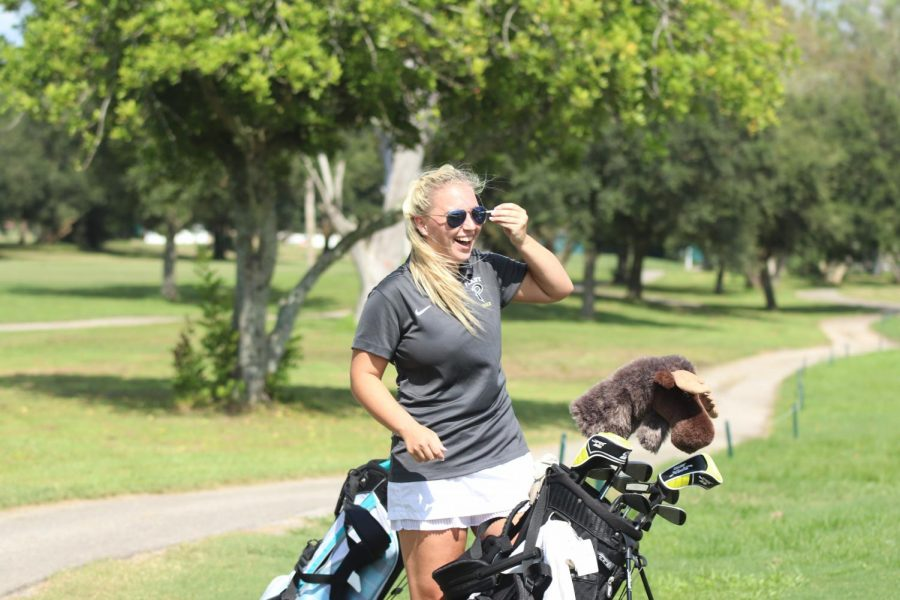 While competing with varsity golf, junior Isabelle McLeod smiles during the tournament. McLeod joined golf her freshman year.