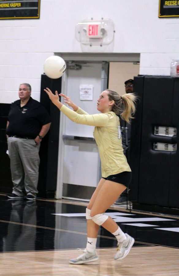 Serving+the+ball%2C+senior+Adele+Cassidy+sends+the+ball+over+the+net+October+23+in+the+gymnasium.+Cassidy+recently+committed+to+Sewanee+University.