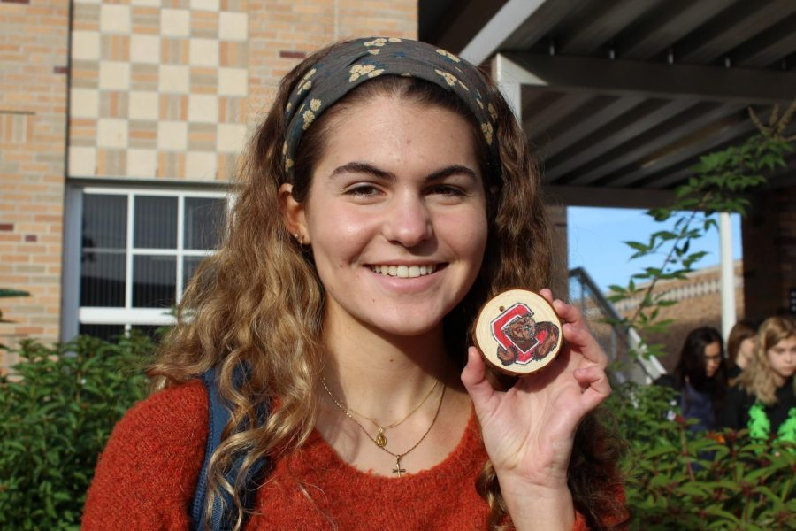 Holding up one of her creations, junior Morgan Austrich smiles while displaying a wooden ornament painted with the Cornell mascot, Touchdown. Austrich is selling the ornaments for fifteen dollars each, with all the proceeds going to the Leukemia and Lymphoma Society.
