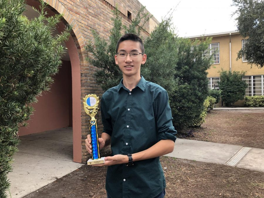Smiling, senior Junhao Zhang holds his trophy from a math competition. Zhang went with a group of other students from Mu Alpha Theta.