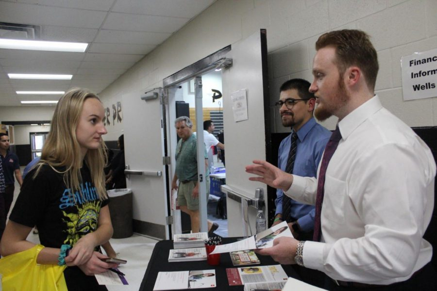 Senior Abby Lynn talks with representatives from the financial aid desk on college night. Students got to visit numerous booths and find out about different scholarships and how to apply for them, as well as ask questions to college representatives.
