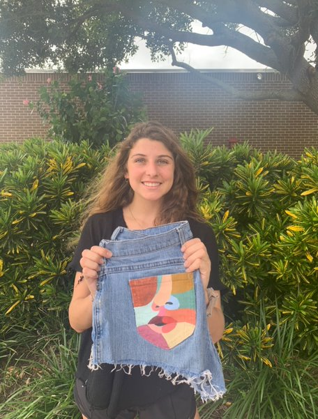 Holding a pair of shorts she recently painted, senior Amelia Spicola shows off the colorful design that she created. Spicola has been selling pairs of shorts and jeans like these since June but has been making them for herself for two years.