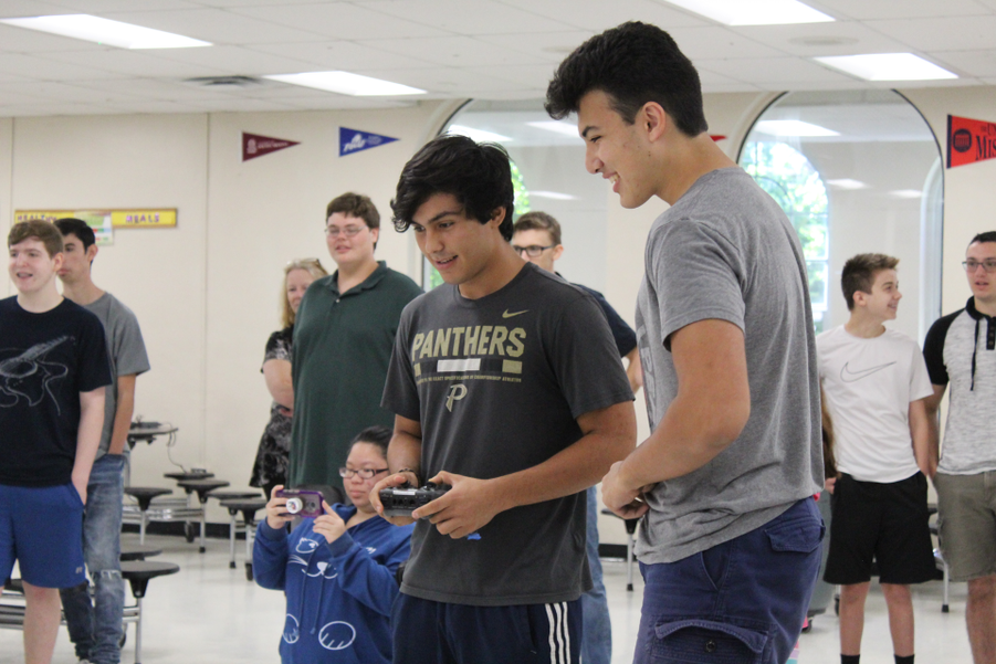 Console in hand, juniors Tristan Aikman and Mateo Craig maneuver their robot during RoboFlag competition, Sept 7. Robotics members helped set up for the meeting beforehand by arranging the arena, setting up the robotics equipment and ensuring all teams had access to the same materials and tools.